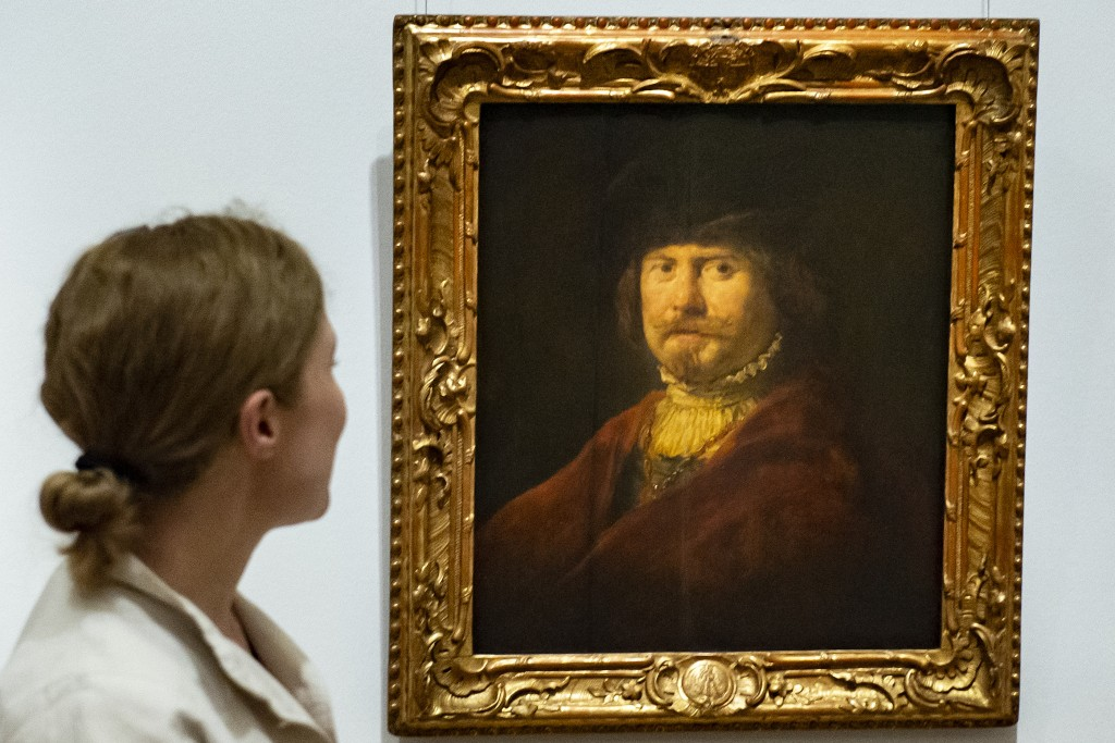 A woman stands in front of the painting 'Rembrandt in a red coat' (c. 1644) by Govaert Flinck during a press preview of the exhibition 'Rembrandt's Ma