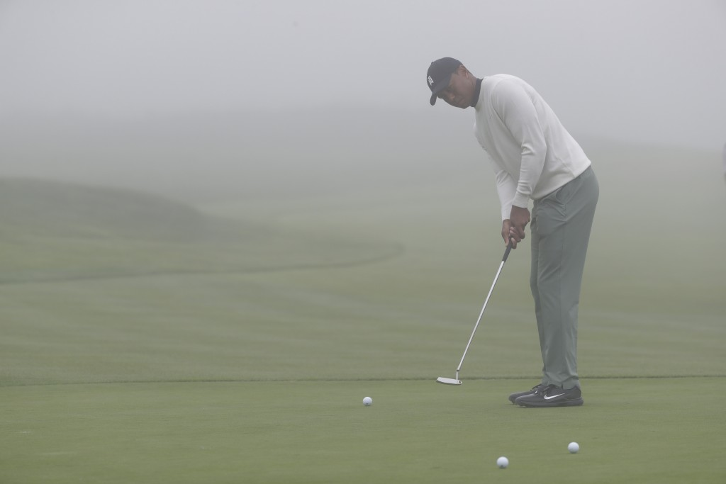 Tiger Woods putts in the fog on the 13th hole duri...