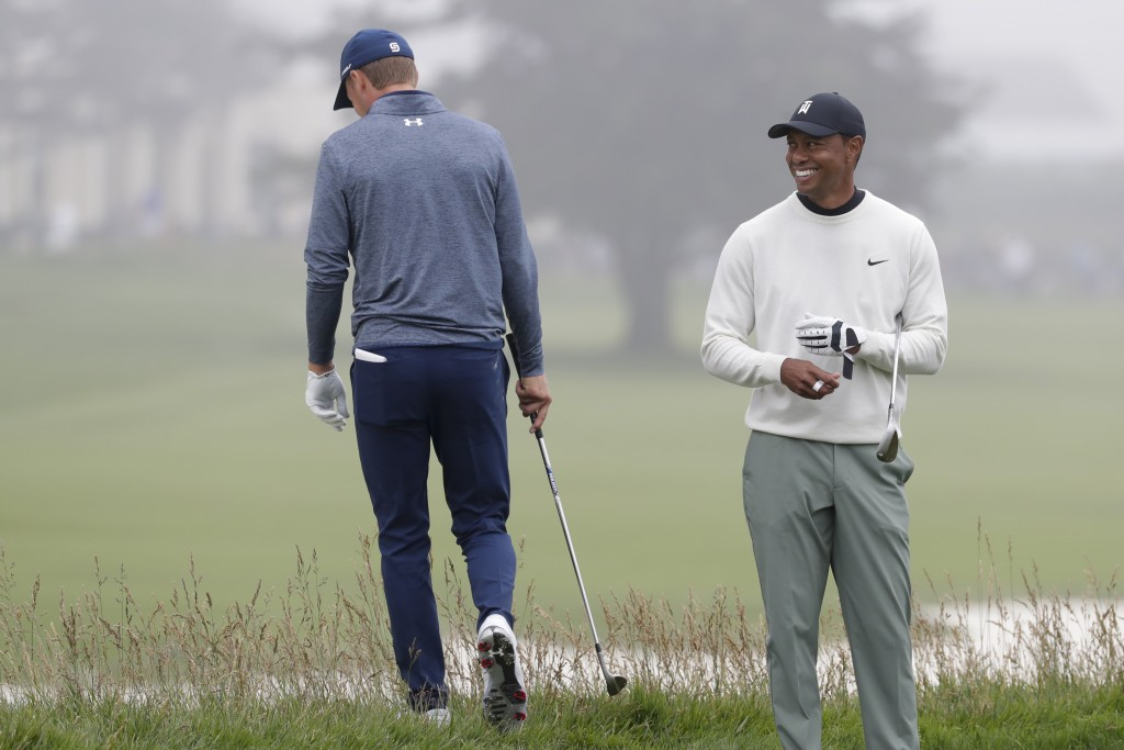 Jordan Spieth, left, walks off the 18th green as Tiger Woods looks on during a practice round for the U.S. Open Championship golf tournament Wednesday