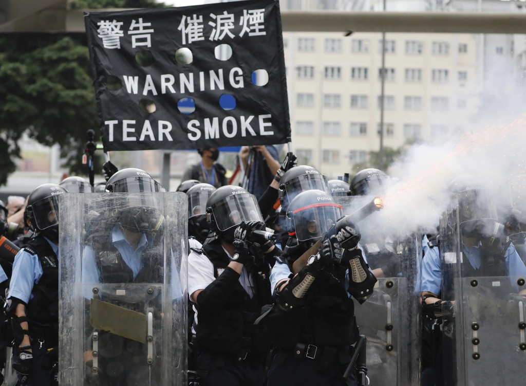 FILE - In this file photo taken Wednesday, June 12, 2019, police fire tear gas towards protesters outside the Legislative Council in Hong Kong. Hong K...