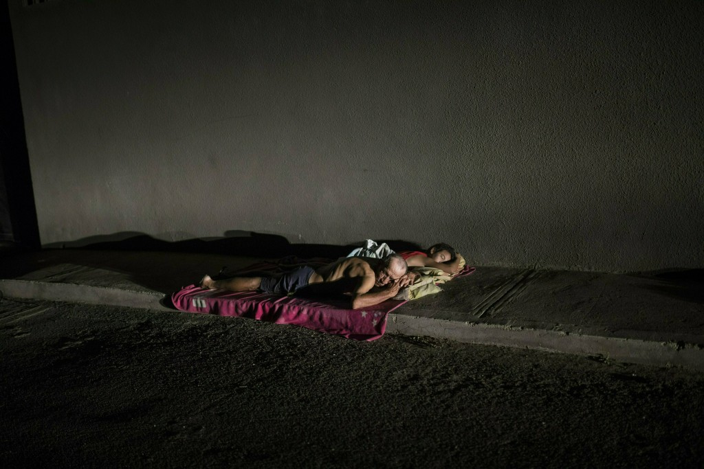 In this May 15, 2019 photo, people sleep on the sidewalk to escape from the heat, due to the lack of electricity in their homes that does not allow th