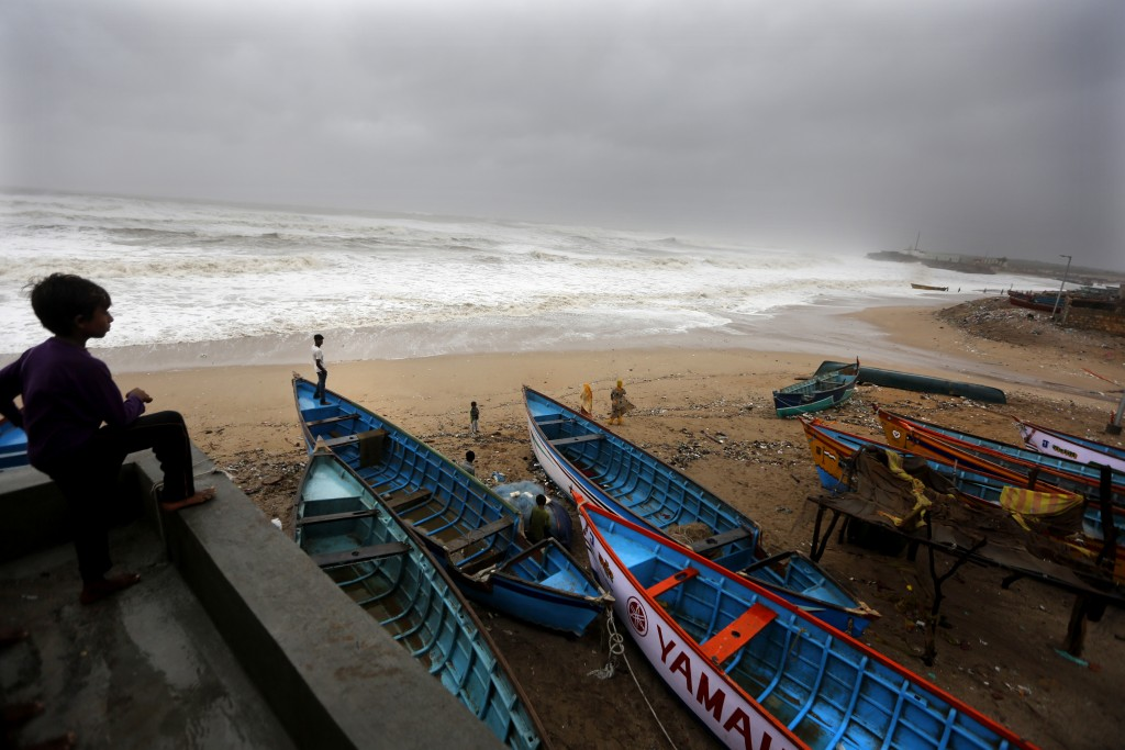 Indians watch as waves crash with shores on the Arabian Sea coast in Veraval, Gujarat, India, Thursday, June 13, 2019. Authorities have evacuated near