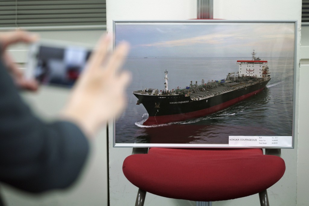 A journalist photographs a picture of the Kokuka Courageous, which was attacked near the Strait of Hormuz, at the Kikuka Sankyo Co., LTD office, owner