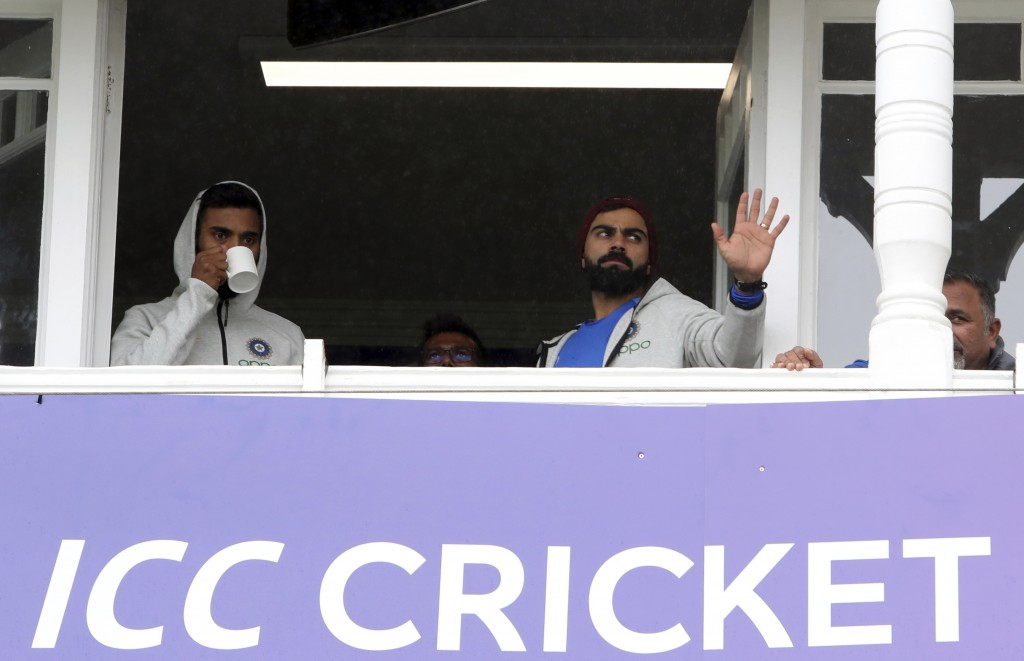 India's captain Virat Kohl, right, with teammate stands in the players pavilion as rain delays start of the Cricket World Cup match between India and