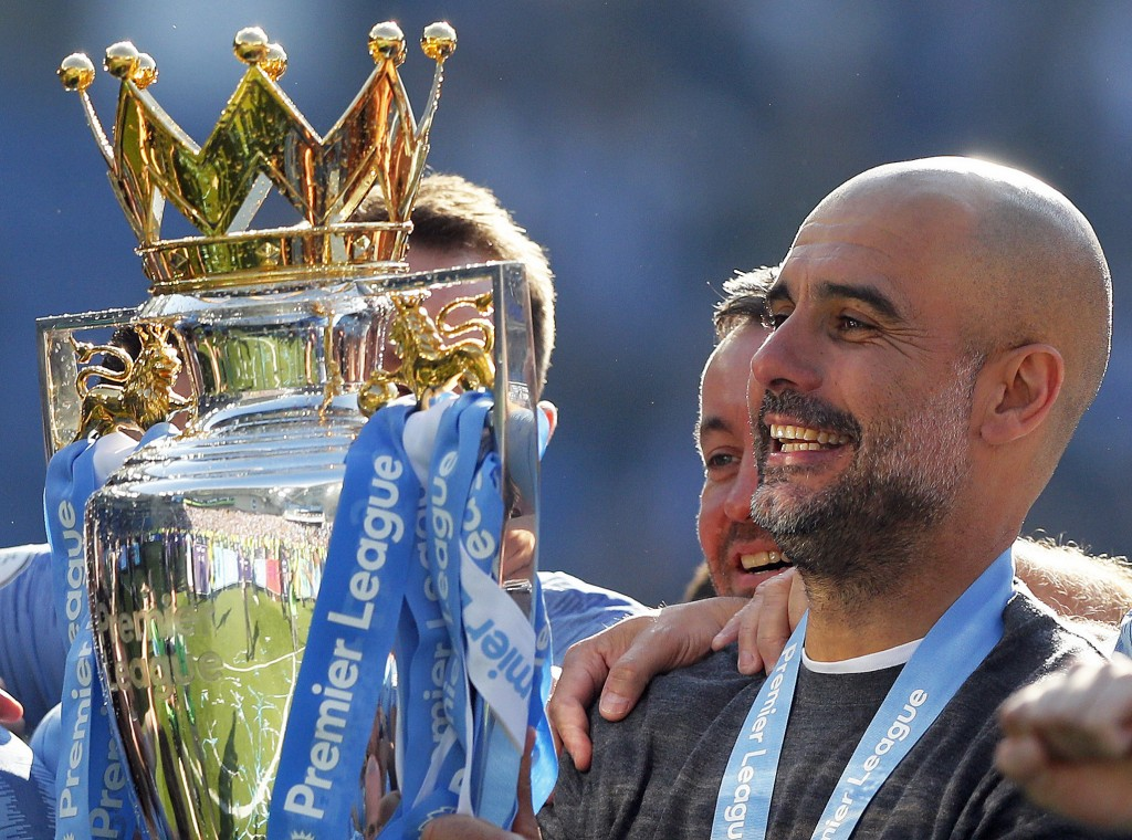 FILE - In this Sunday, May 12, 2019 file photo, Manchester City coach Pep Guardiola lifts the English Premier League trophy after the English Premier