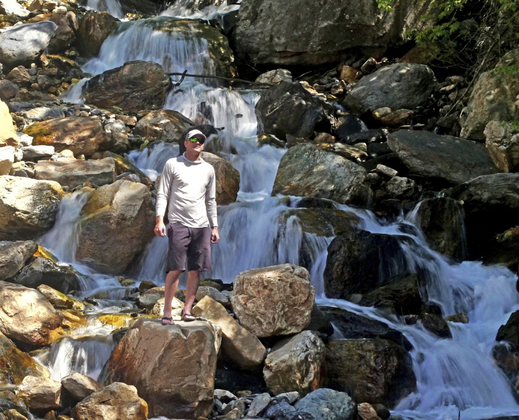 This Monday, June 10, 2019, photo shows hiker Tony Larsen posing for a photograph at a waterfalls, in the Big Cottonwood canyon, near Salt Lake City.