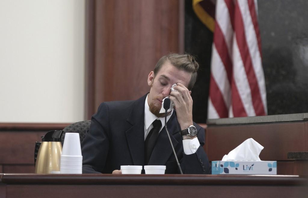 Tyler Jones wipes his eyes while testifying during...