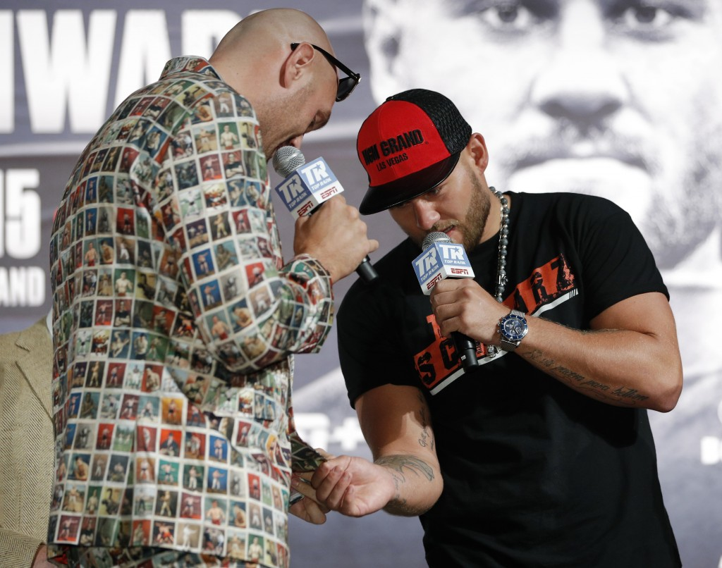 Tom Schwarz, right, of Germany, looks at the suit of Tyson Fury, of England, during a news conference for their upcoming fight Wednesday, June 12, 201
