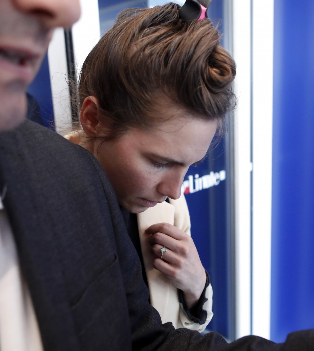 Amanda Knox is escorted as she arrives in Linate airport, Milan, Italy, Thursday, June 13, 2019. Knox has returned to Italy for the first time since s
