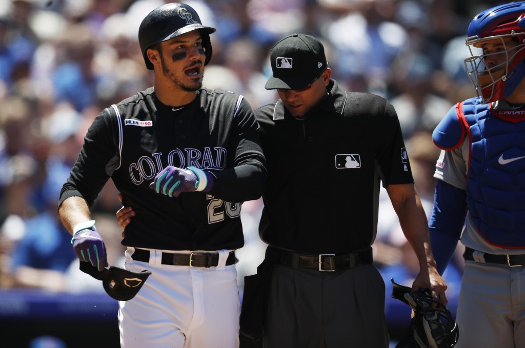 Colorado Rockies' Nolan Arenado, left, reacts after getting hit by a pitch from Chicago Cubs starting pitcher Cole Hamels as home plate umpire Roberto