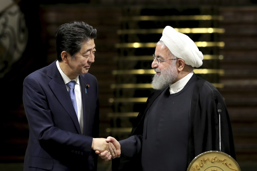 Japanese Prime Minister Shinzo Abe, left, and Iranian President Hassan Rouhani shake hands after their joint press conference at the Saadabad Palace i
