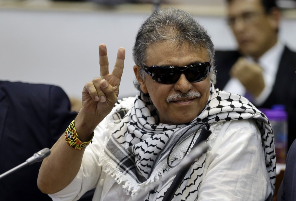FILE - In this June 12, 2019 file photo, former FARC rebel Jesus Santrich gives a victory signal to journalists as he attends a session of the Chamber...