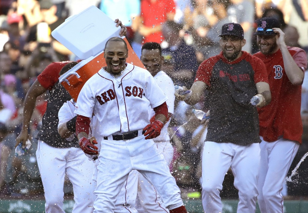 Boston Red Sox's Mookie Betts is doused by teammates after drawing a game-ending walk that gave the team a 4-3 win against the Texas Rangers in a base...