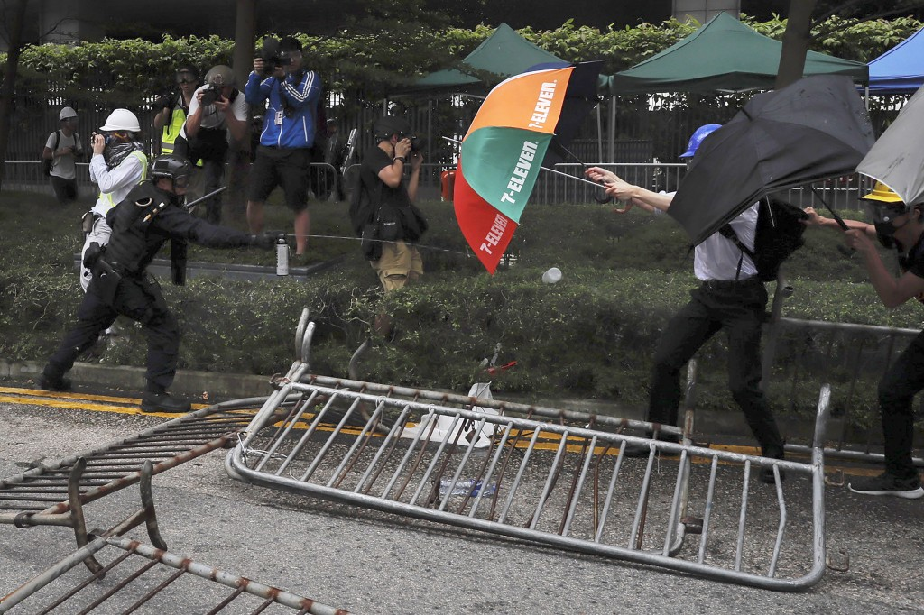 FILE - In this file photo taken Wednesday, June 12, 2019, a police officer sprays pepper spray at protesters using an umbrella for protection near the