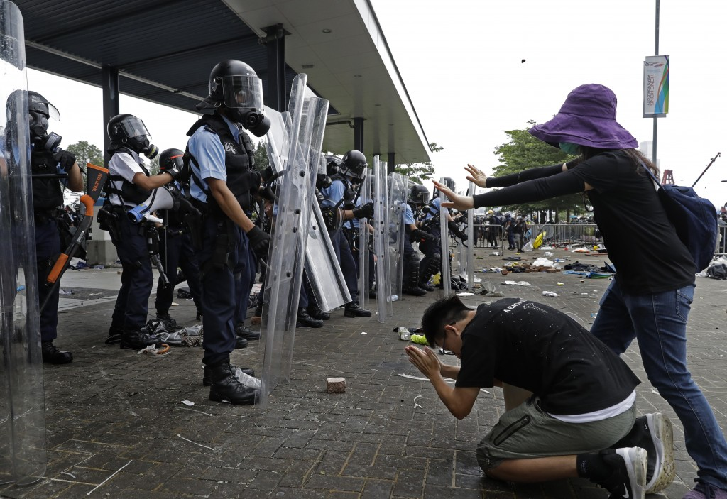 FILE - In this file photo taken Wednesday, June 12, 2019, a protester bows to riot police after they fire tear gas towards protesters outside the Legi