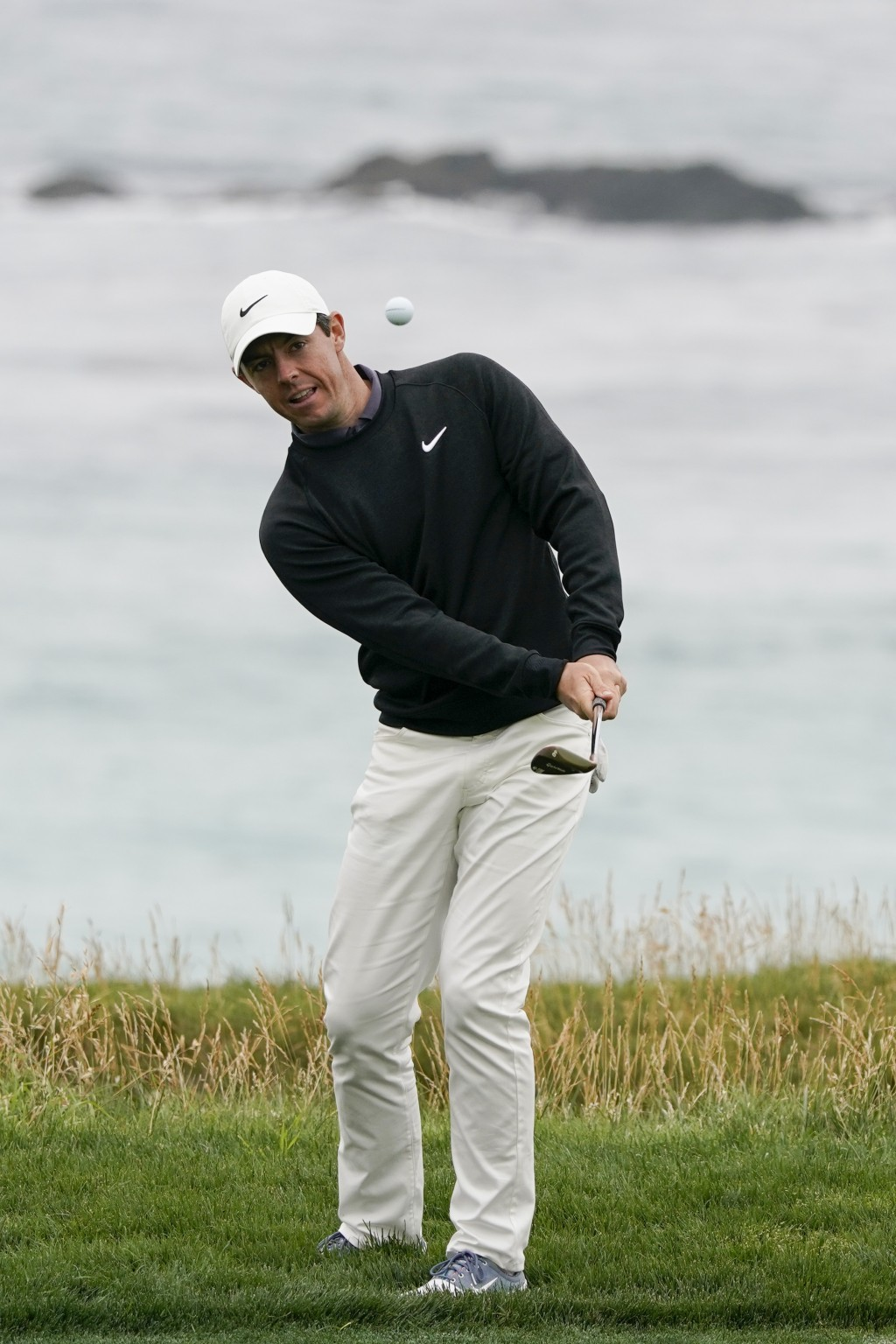 Rory McIlroy, of Northern Ireland, hits a chip shot on the 10th hole during a practice round for the U.S. Open Championship golf tournament Wednesday,...