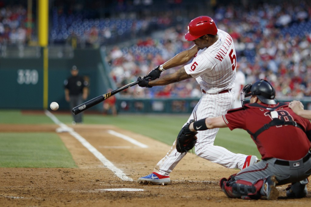 Philadelphia Phillies' Nick Williams, left, breaks his bat on a single during the fifth inning of the team's baseball game against the Arizona Diamond...