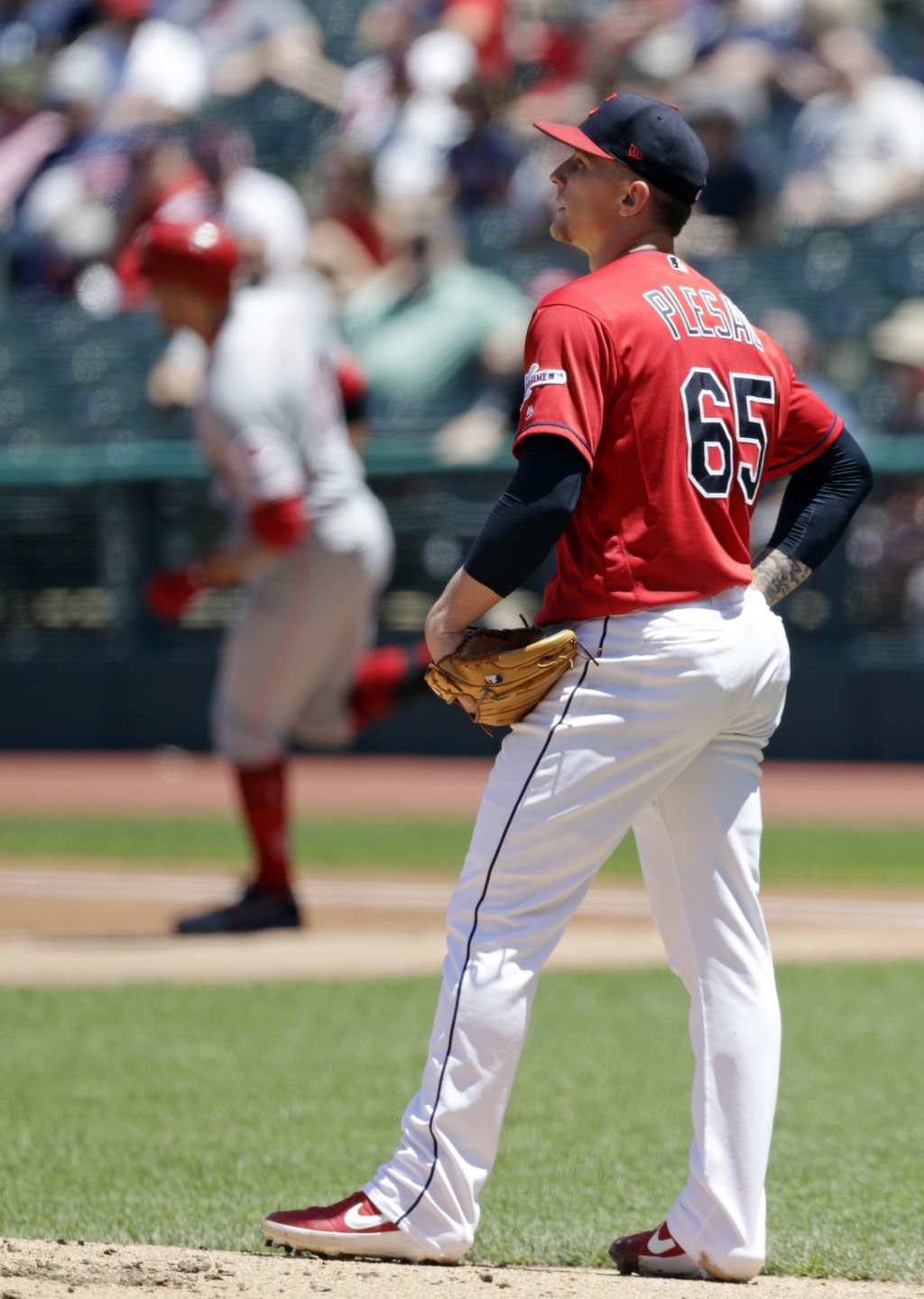 Cleveland Indians starting pitcher Zach Plesac, right, waits for Cincinnati Reds' Joey Votto to run the bases after Votto hit a solo home run in the f...