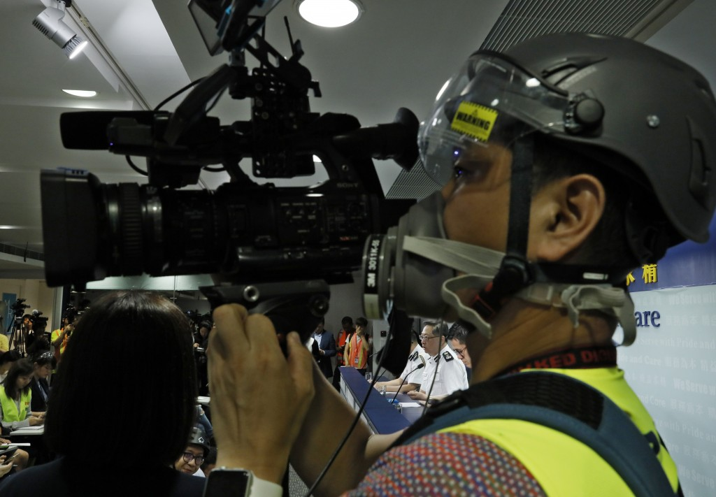 A press cameraman wears a helmet for protection in the clashes seen in recent protests, films a press conference by Commissioner of Police Stephen Lo