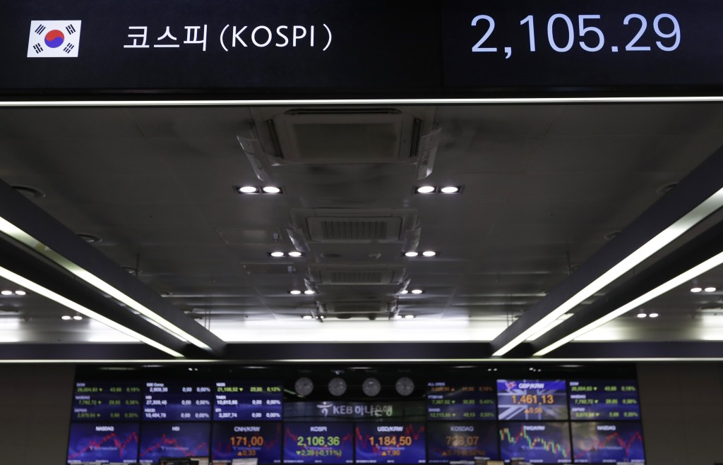 The screen, top, showing the Korea Composite Stock Price Index (KOSPI) is seen at the foreign exchange dealing room in Seoul, South Korea, Thursday, J...