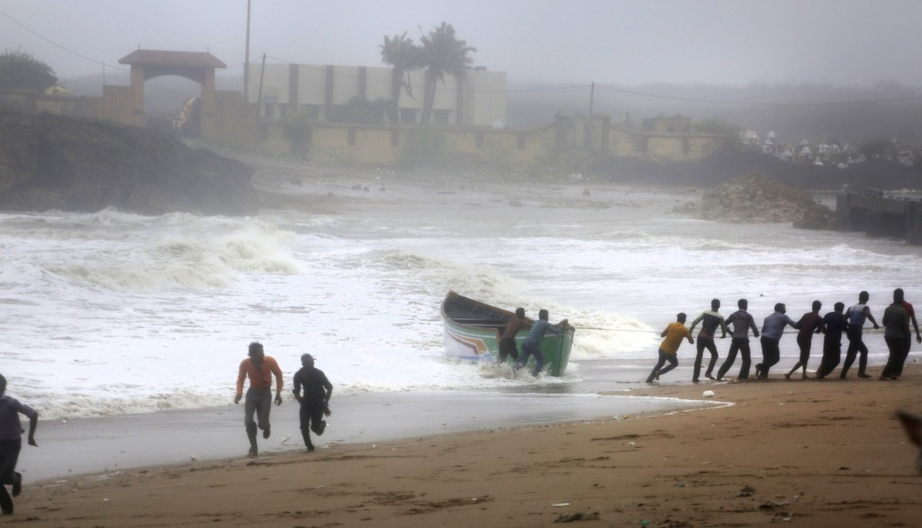 People try to pull back a fishing boat that was carries away by waves on the Arabian Sea coast as others run to take shelter in Veraval, Gujarat, Indi