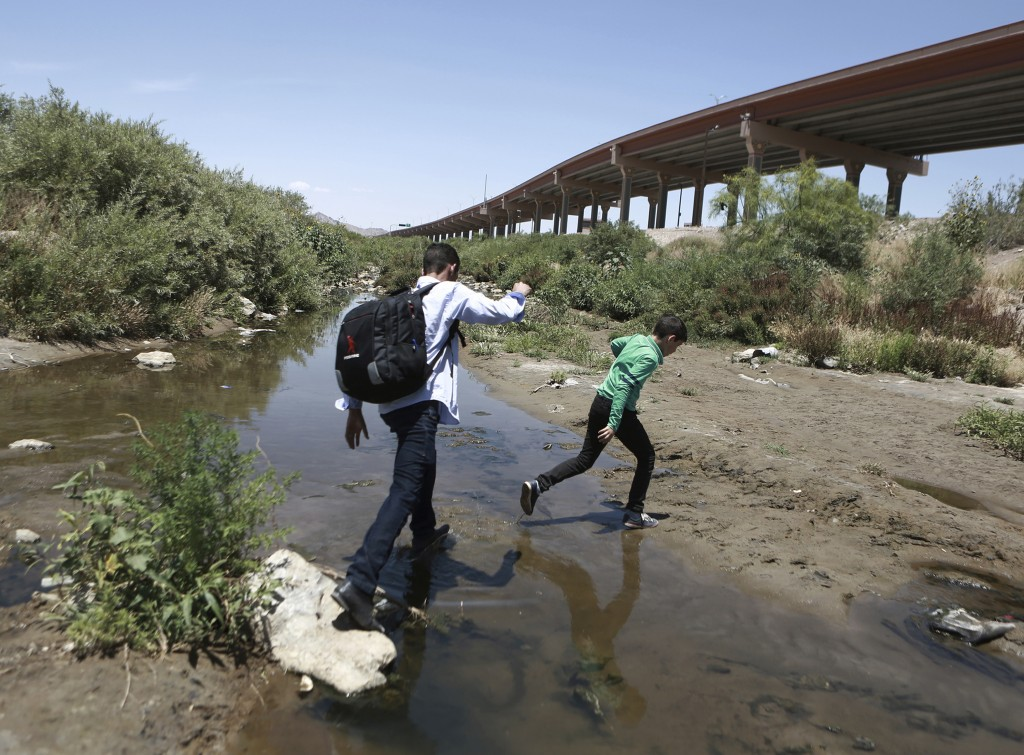 FILE - In this June 7, 2019 file photo, people cross the Rio Grande into the United States to turn themselves over to authorities and ask for asylum,
