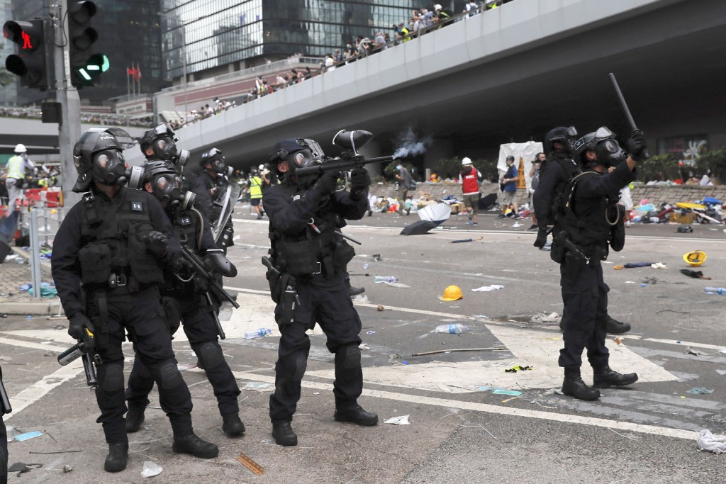 FILE - In this file photo taken Wednesday, June 12, 2019, a policeman fires with a pepper ball gun towards protesters near the Legislative Council in