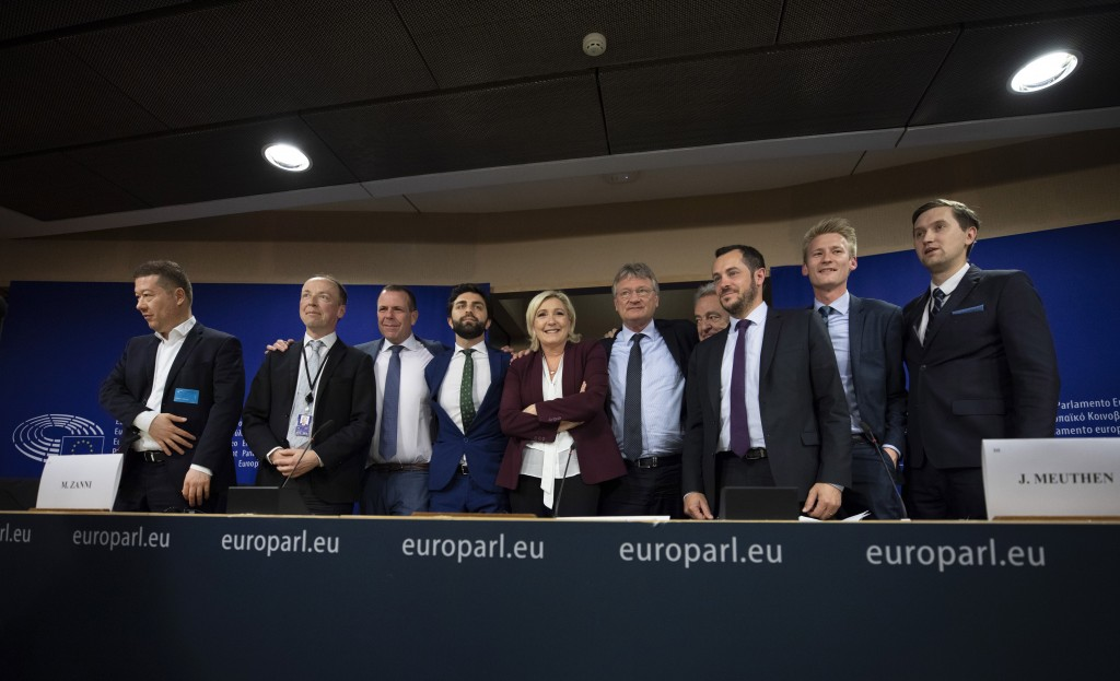 French far-right National Rally leader and MEP Marine Le Pen, center, poses with other far-right members during a media conference to announce the for