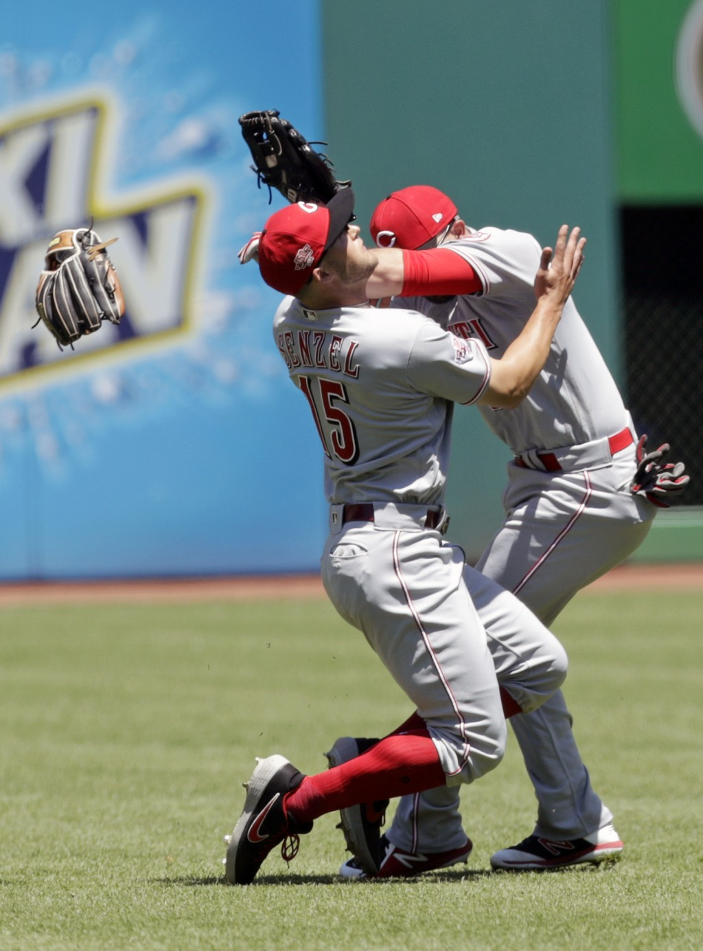 Cincinnati Reds' Nick Senzel, left, and Jose Peraza collide going after a ball hit by Cleveland Indians' Francisco Lindor in the first inning in a bas...