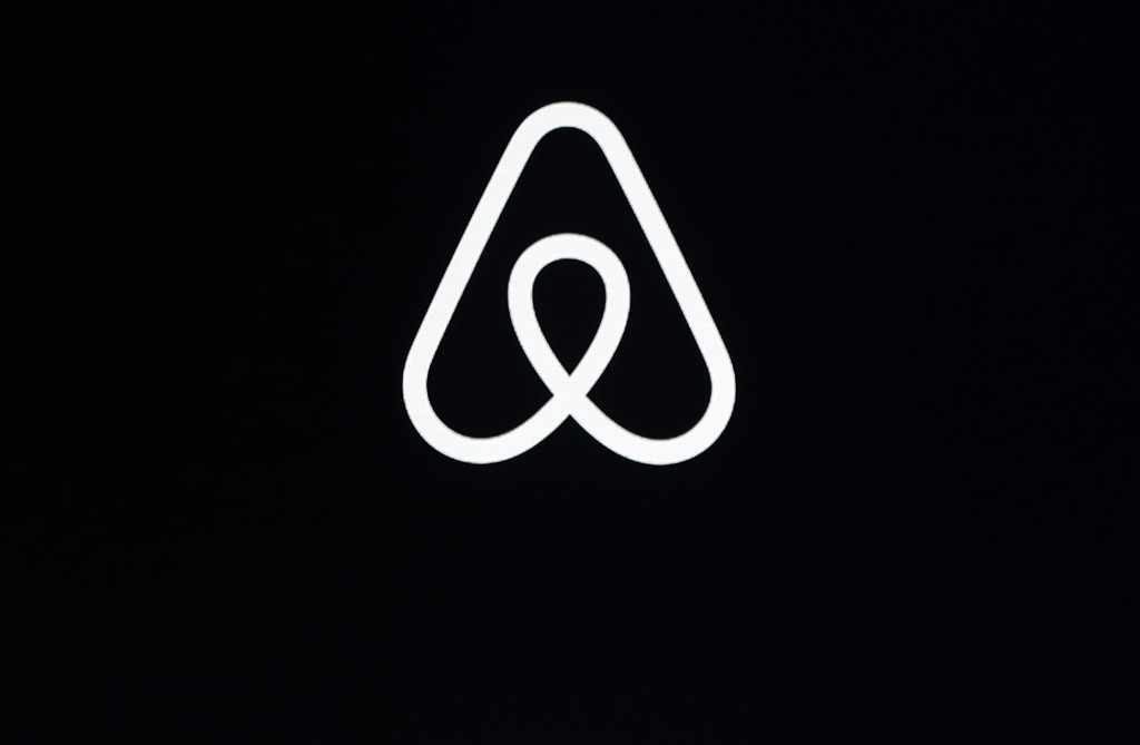 FILE - This Feb. 22, 2018, file photo shows an Airbnb logo during an event in San Francisco. A lucky few will be able to live the adventures of Philea...