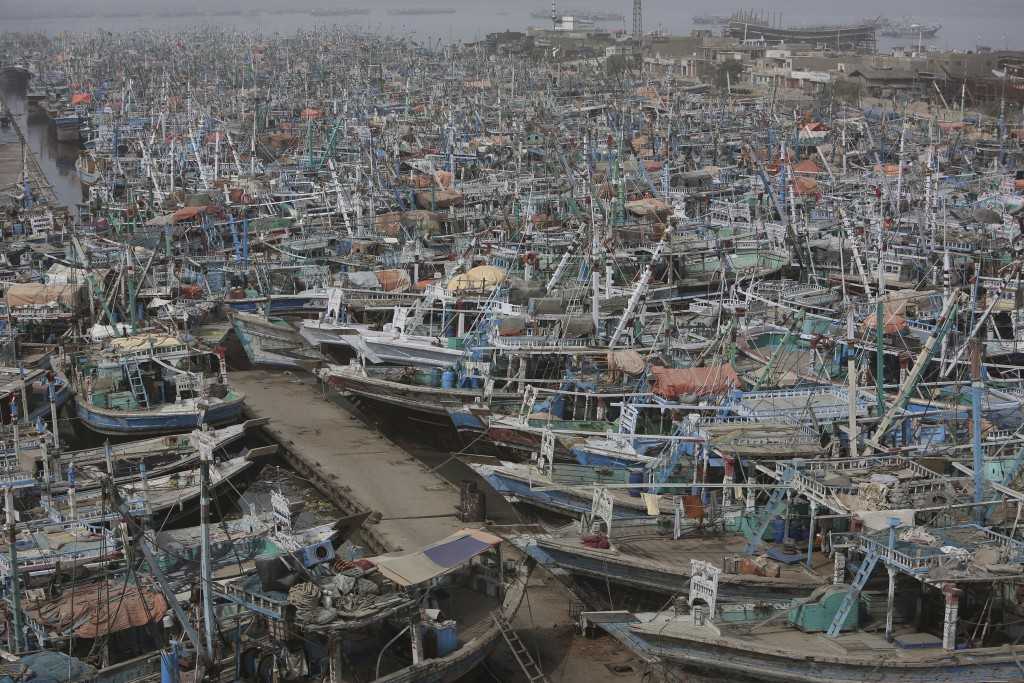 Pakistani fishing boats are called back from the sea following a warning by authorities of Cyclone Vayu at Karachi harbor in Pakistan, Thursday, June