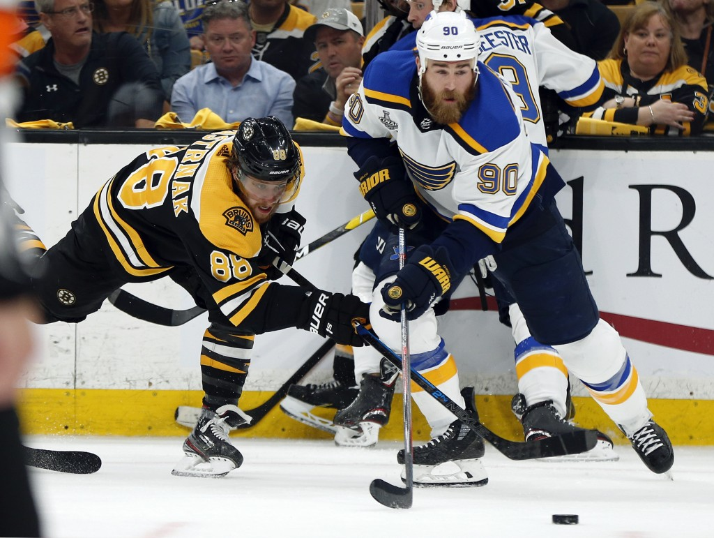 St. Louis Blues' Ryan O'Reilly (90) moves the puck away from Boston Bruins' David Pastrnak, left, of the Czech Republic, during the second period in G...