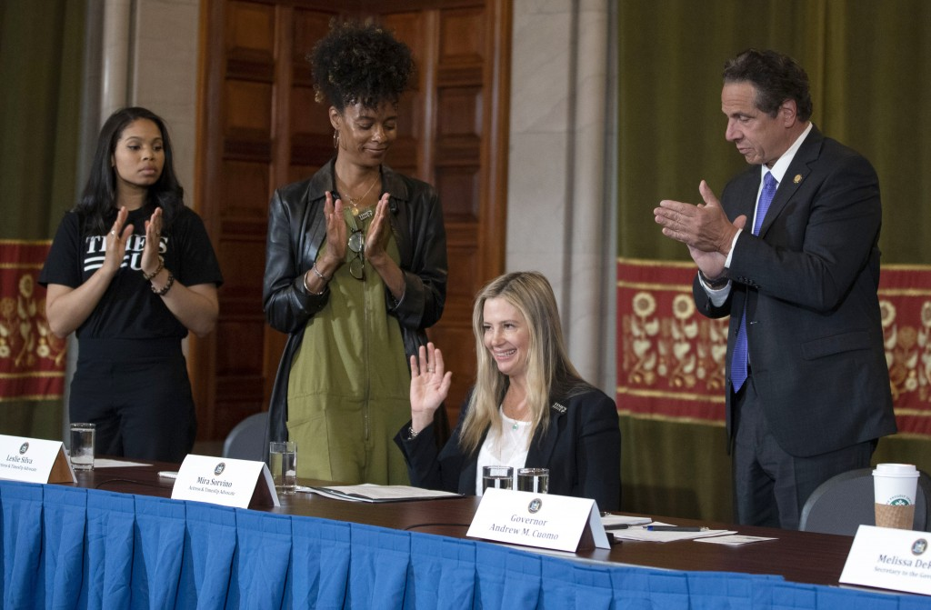 New York Governor Andrew Cuomo, right, applauds Oscar-winning actress Mira Sorvino as she joined Times's Up advocates speaking out about sexual assaul