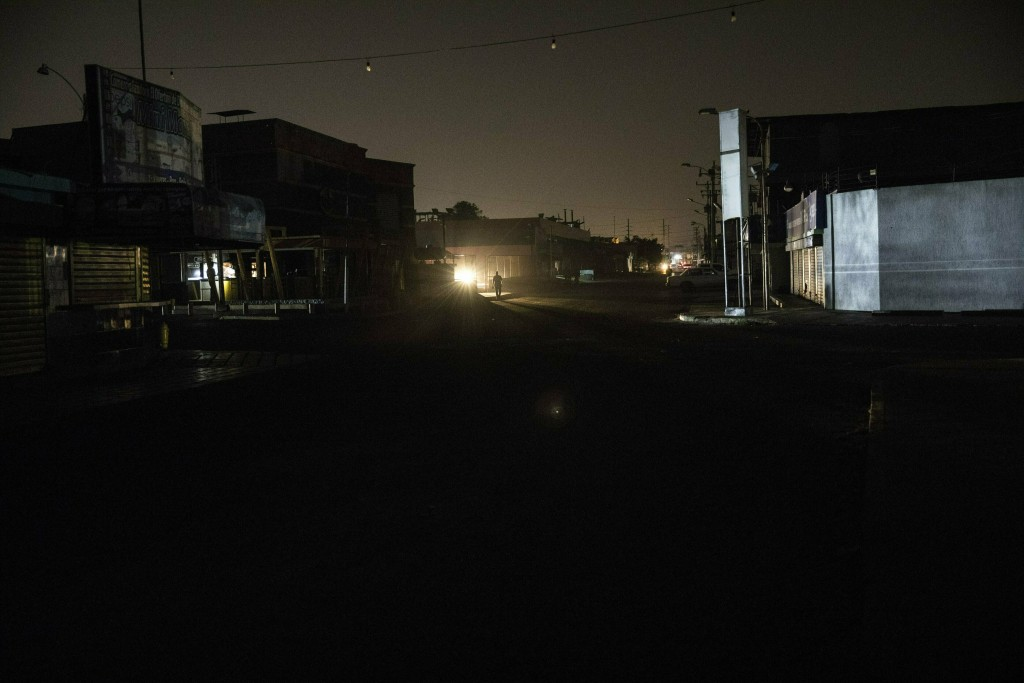 In this May 21, 2019 photo, a man walks in a dark downtown Maracaibo, Venezuela, during a black out. The situation is especially dire in Maracaibo, on