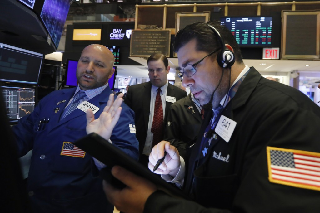 FILE- In this June 6, 2019, file photo specialist John Parisi, left, works with traders on the floor of the New York Stock Exchange. The U.S. stock ma...