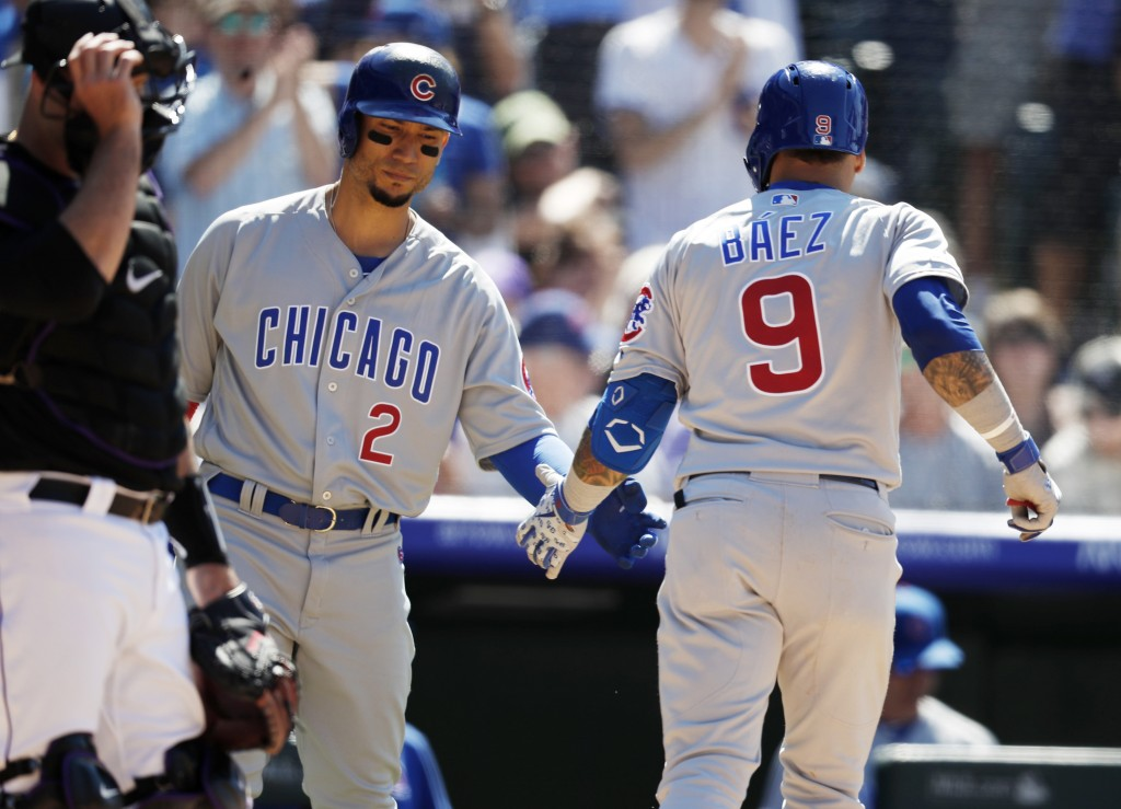 Chicago Cubs' Carlos Gonzalez, left, congratulates Javier Baez as he returns to the dugout after hitting a two-run home run off Colorado Rockies relie
