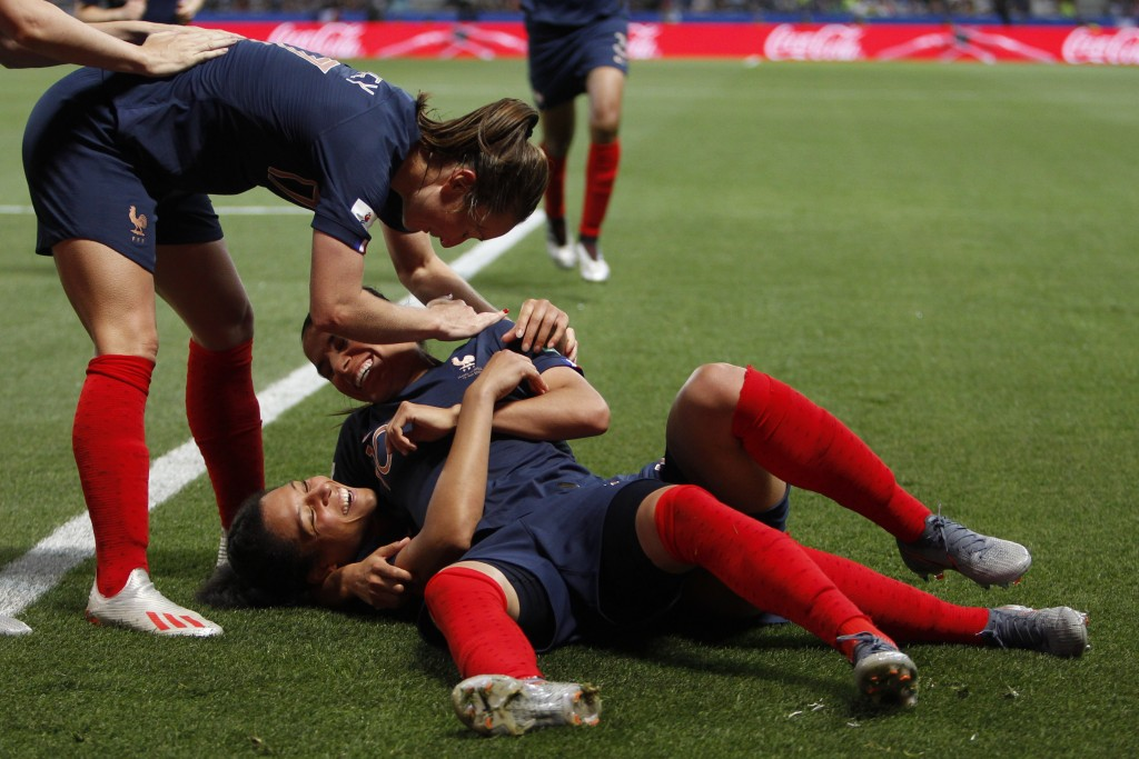 France's Valerie Gauvin, on the pitch, celebrates with her teammates after scoring her side's opening goal during the Women's World Cup Group A soccer