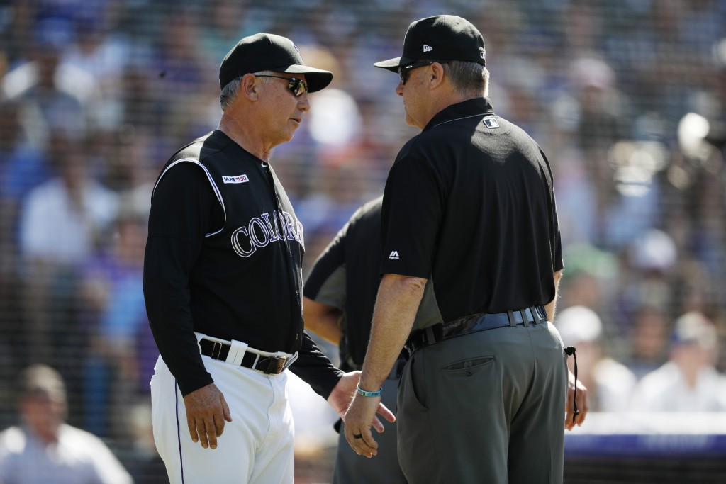 Colorado Rockies manager Bud Black, left, confers with third base umpire Gary Cederstrom after Chicago Cubs relief pitcher Brad Brach hit Colorado's T...