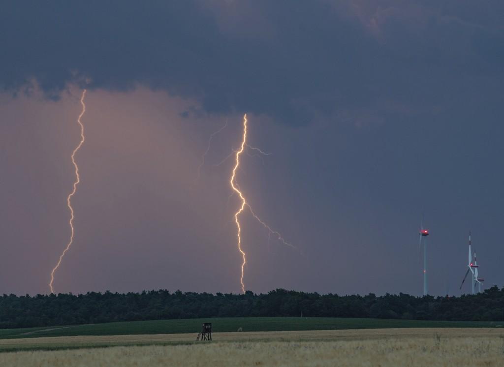 Lightning strikes over a field near wind turbines ...