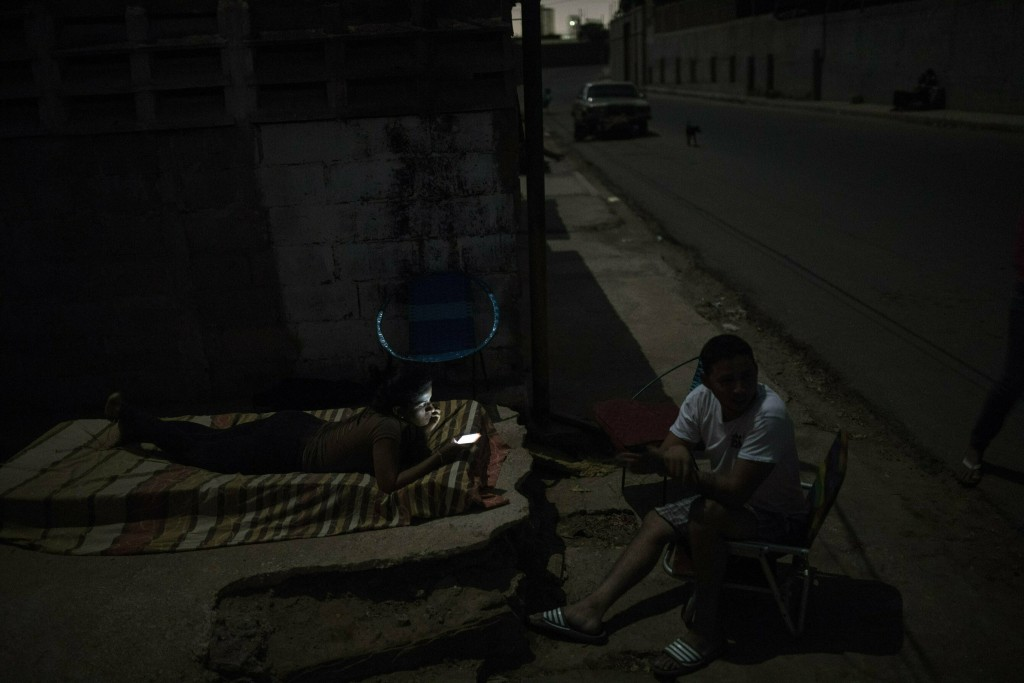 In this May 15, 2019 photo, Marjorie Marcano uses her cell phone while preparing to sleep on a mattress on the sidewalk outside her home, due to a bla