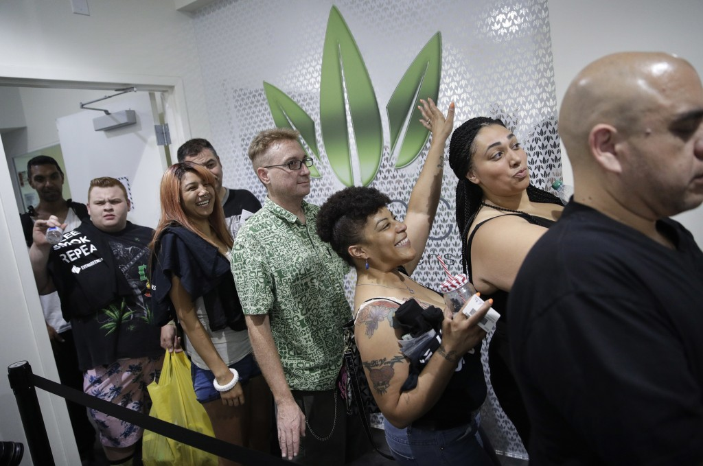 FILE - In this July 1, 2017, file photo, people wait in line at the Essence cannabis dispensary in Las Vegas. Nevada is set to pioneer a law to preven