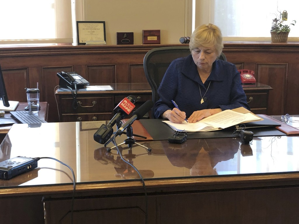 Maine Democratic Gov. Janet Mills signs a bill Wednesday, June 12, 2019, in her office in Augusta, Maine, becoming the eighth state to allow terminall...