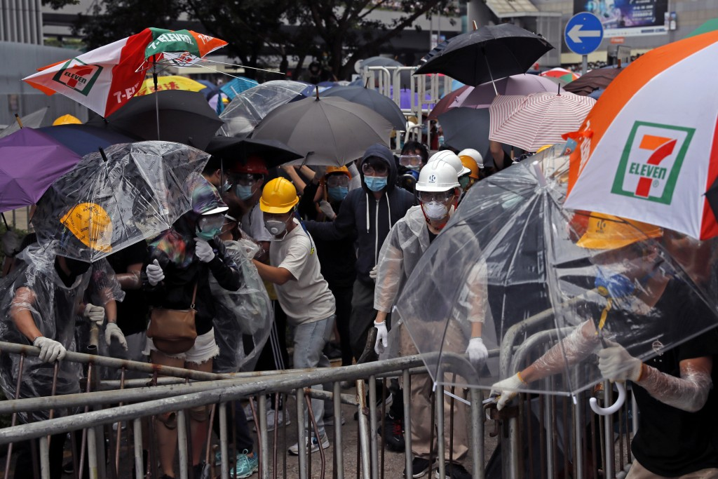 In this photo taken on Wednesday, June 12, 2019, protestors wear masks and helmets and hold umbrellas to protect their identities and provide cover fr