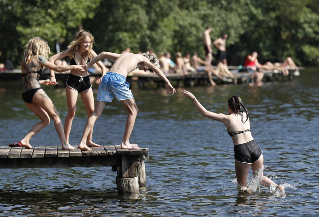 People sunbathe enjoying warm weather on a lake near Vilnius, Lithuania, Wednesday, June 12, 2019. A heat wave continues in Lithuania as temperatures