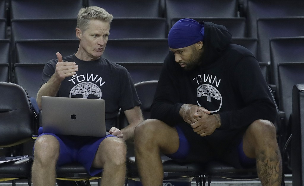 Golden State Warriors head coach Steve Kerr, left, talks with center DeMarcus Cousins during a team practice in Oakland, Calif., Wednesday, June 12, 2