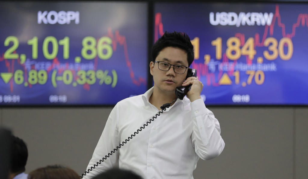 A currency trader talks on the phone near the screens showing the Korea Composite Stock Price Index (KOSPI), left, and the foreign exchange rate betwe
