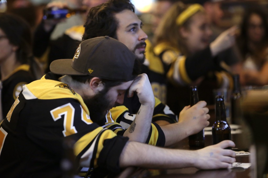 Boston Bruins fan Adam Aldred, front, of Foxborough, Mass., rests his head on his hand at a Boston bar, after the St. Louis Blues defeated the Bruins