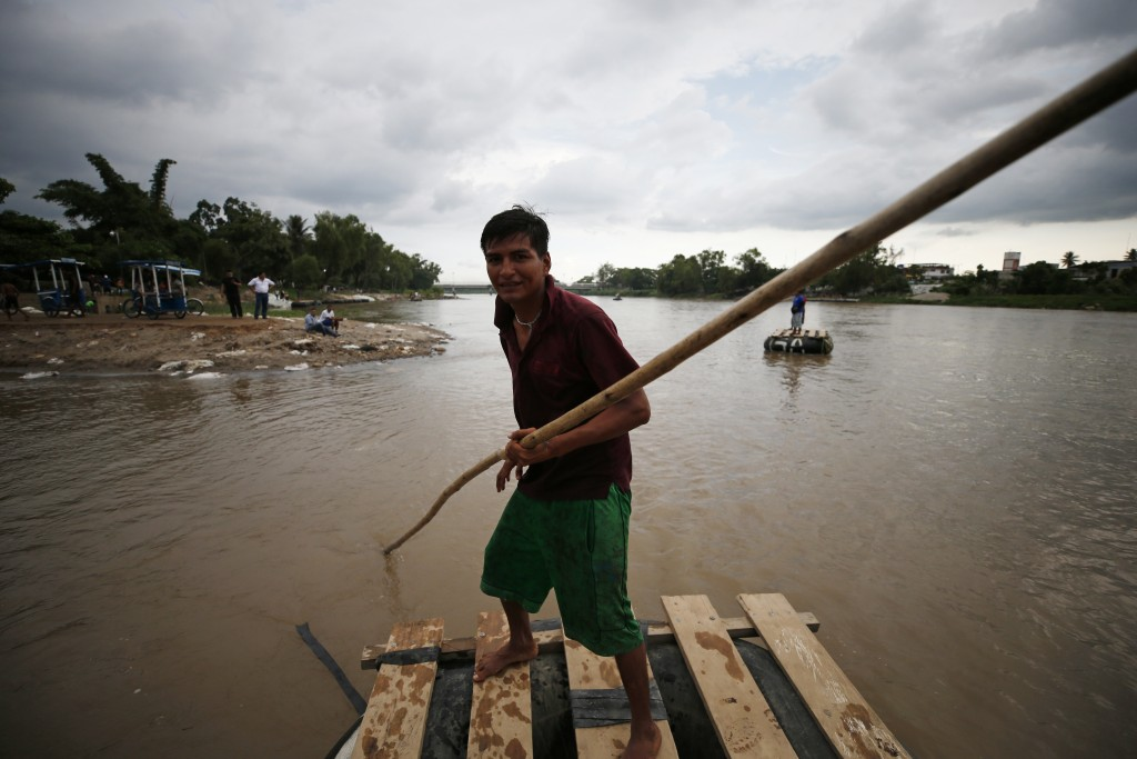 A Mexican raft operator, not permitted to carry passengers or merchandise back from Guatemala, returns empty-handed across the Suchiate River toward C
