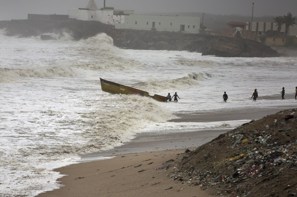 People try to pull back a fishing boat that was carries away by waves on the Arabian Sea coast in Veraval, Gujarat, India, Thursday, June 13, 2019. Au