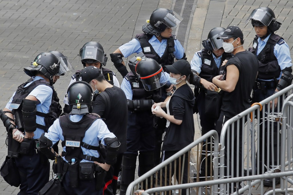 Riot police check the bags of protesters outside the Legislative Council in Hong Kong, Thursday, June 13, 2019. After days of silence, Chinese state m